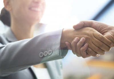 Two business people shaking hands and smiling